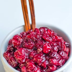 Low carb cranberry sauce in a white bowl with cinnamon sticks