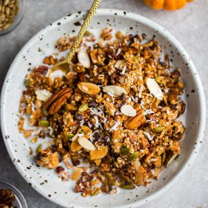 Top view keto pumpkin granola in a white bowl with a gold spoon