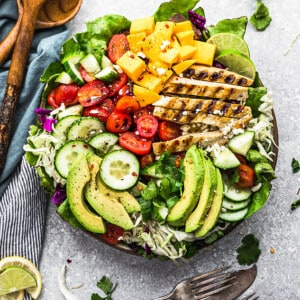Top view of a loaded grilled mango chicken salad in a bowl with two forks