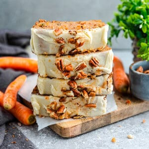 Side view of 4 stacked carrot loaf slices on a wooden cutting board