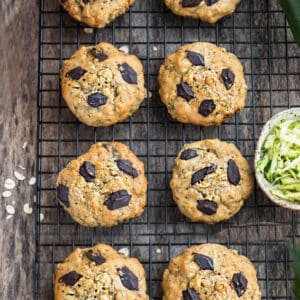 Top view of zucchini cookies on a black wire rack on a wooden board