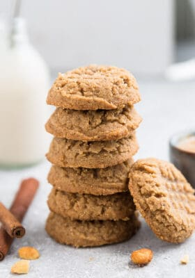 Side view of 5 stacked keto peanut butter cookies with one keto peanut butter cookie leaning on the stack on a grey background with a milk bottle in the background