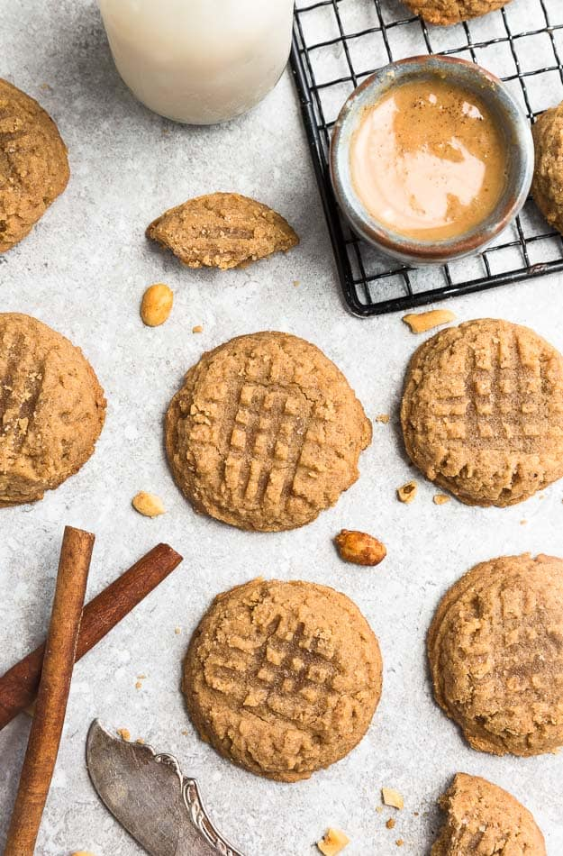 Keto peanut butter cookies arranged on a counter with cinnamon sticks and peanut butter