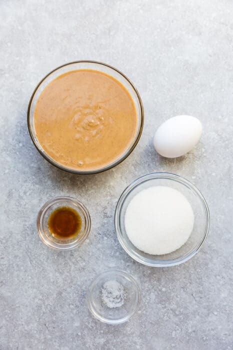 Top view of ingredients to make keto peanut butter cookies on a grey background: peanut butter, egg, monk fruit sweetener, vanilla and salt