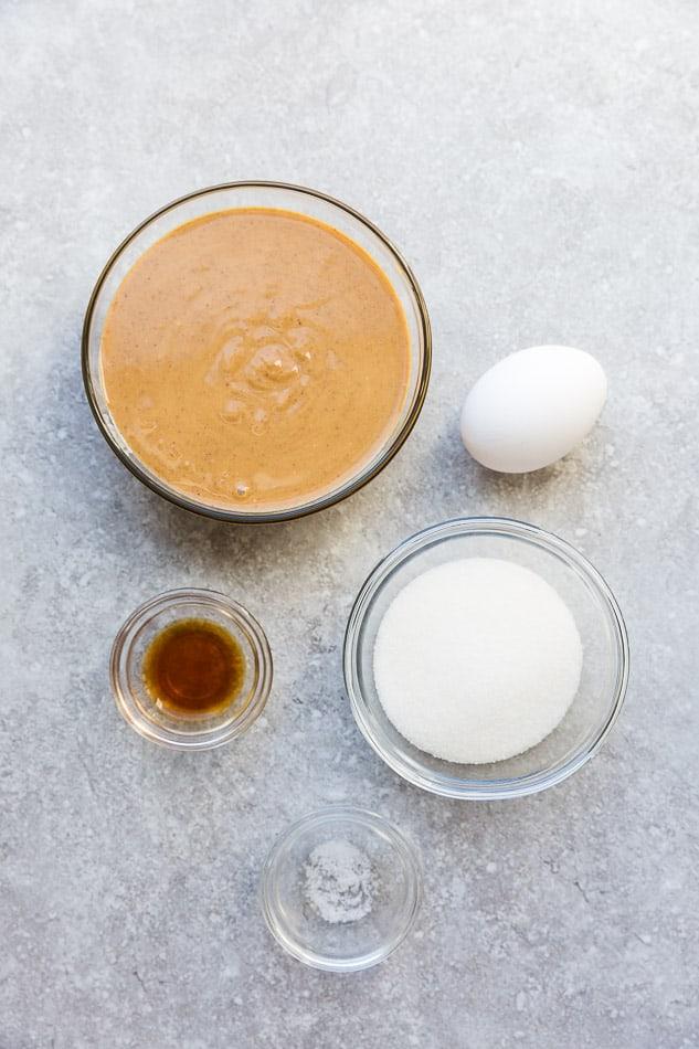 Peanut butter, an egg, vanilla, monk fruit sweetener and salt arranged on a countertop