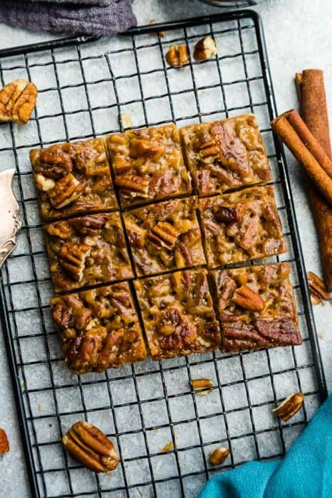 Top view of keto pecan pie bars cut into nine squares on wire rack on a grey backgroud