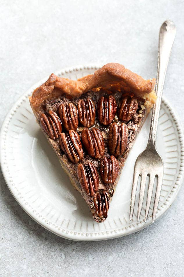 Slice of Keto Pecan Pie on a white plate with a fork