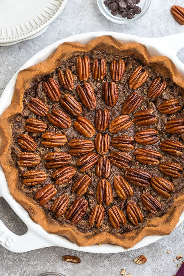 Close-up view of Keto Pecan Pie in a white pie pan on a grey background