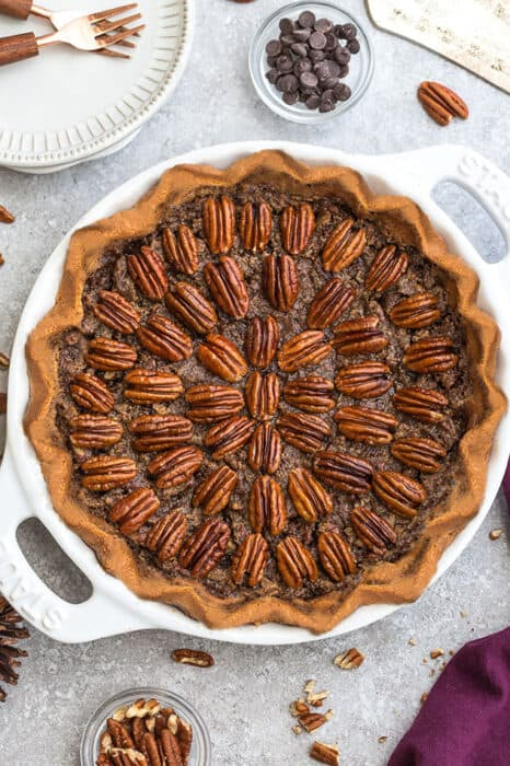 Top view of Keto Pecan Pie in a white pie pan on a grey background