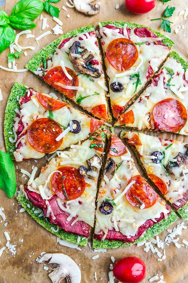 Close-up top view of sliced baked Broccoli Pizza Crust with tomato sauce, cheese, mushrooms, olives and pepperoni on brown parchment paper on a baking sheet