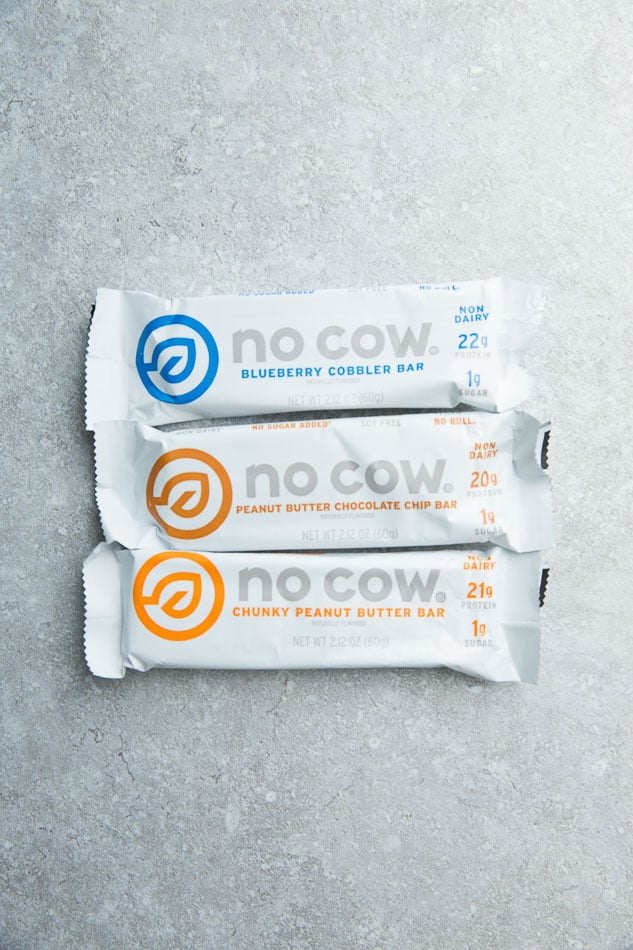 Top view of three No Cow Protein Bars on a grey background