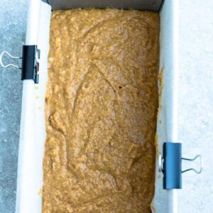 Top view of a 9x5 loaf pan lined with parchment paper with pumpkin bread batter
