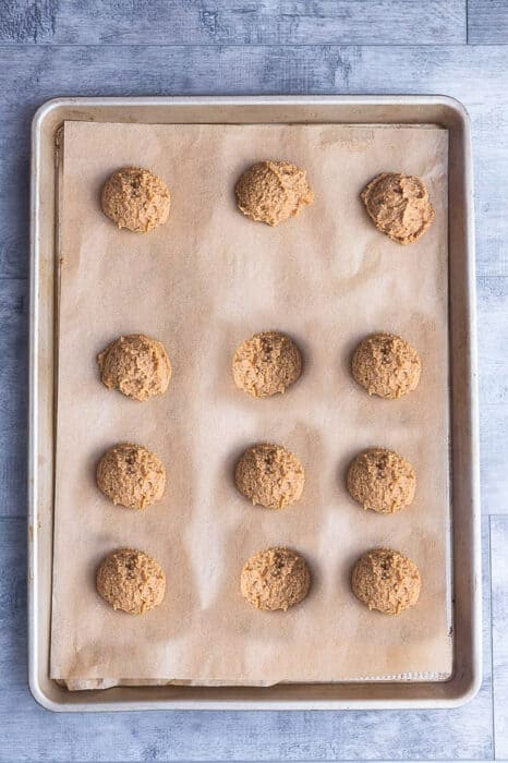 Top view of 12 unbaked keto pumpkin cookies on a baking sheet