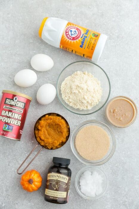 Top view of ingredients to make low carb keto pumpkin cookies with chocolate chips on a grey background