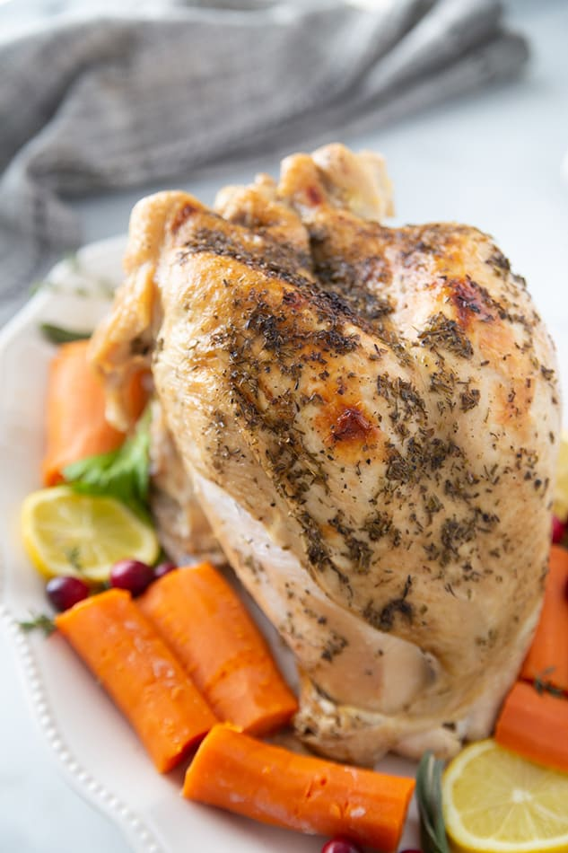 Side close-up view of Instant Pot Turkey breast on a white plate with vegetables