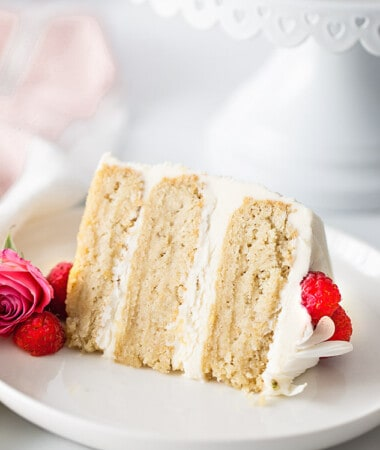 A slice of Keto Vanilla Cake on a white plate garnished with fresh raspberries