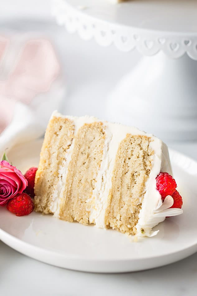 A slice of Keto Vanilla Cake on a white plate garnished with raspberries