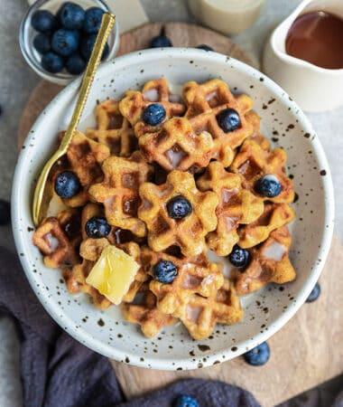 Top view of gluten-free waffle cereal in a white bowl with blueberries, butter, milk and maple syrup and a gold spoon