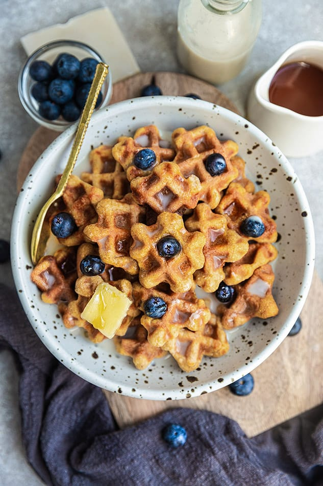 Overhead image of waffle cereal topped with blueberries, butter, and syrup.
