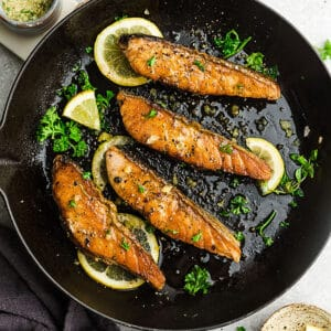 Top view of broiled salmon in a cast-iron skillet