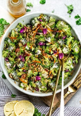 Top view of Keto broccoli salad in a white bowl with gold spoons