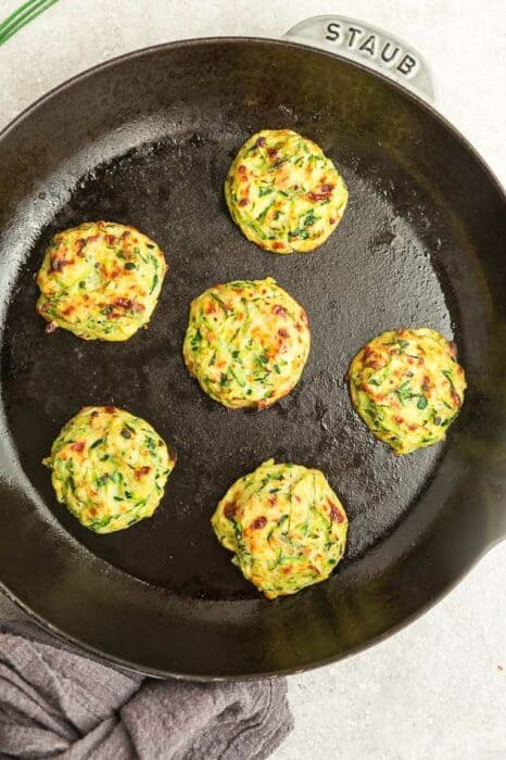 Top view of fried zucchini fritters in a cast iron pan