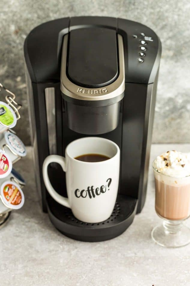 A Keurig machine with a brewed cup of coffee in it