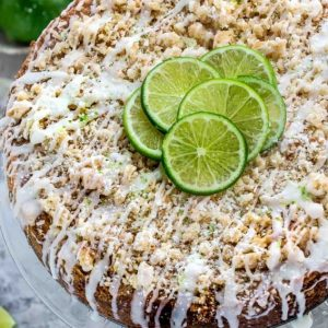 Overhead view of Key lime coffee cake with white chocolate drizzle on a clear glass plate topped with lime slices
