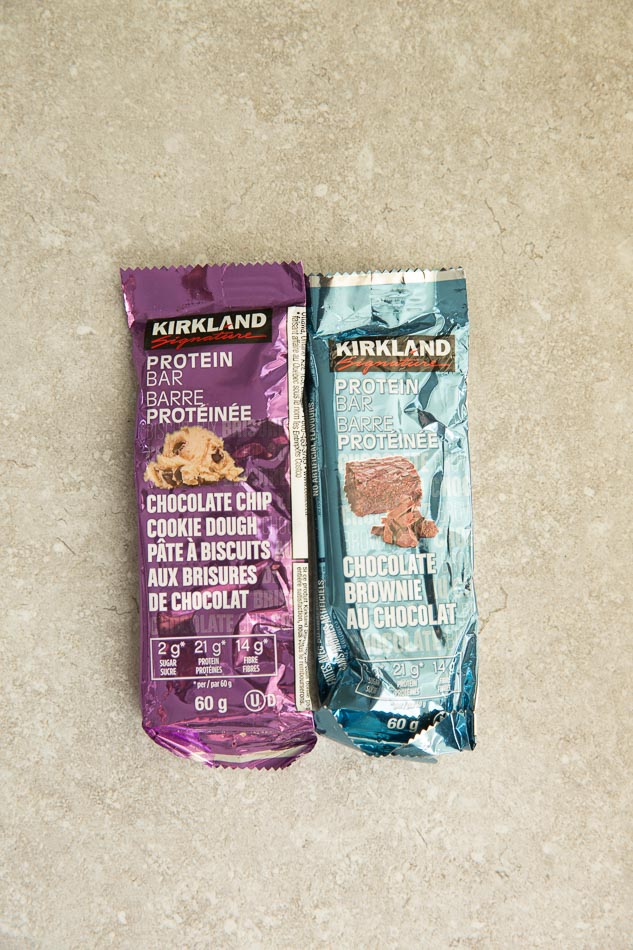 Two Kirkland Protein Bars on a gray background