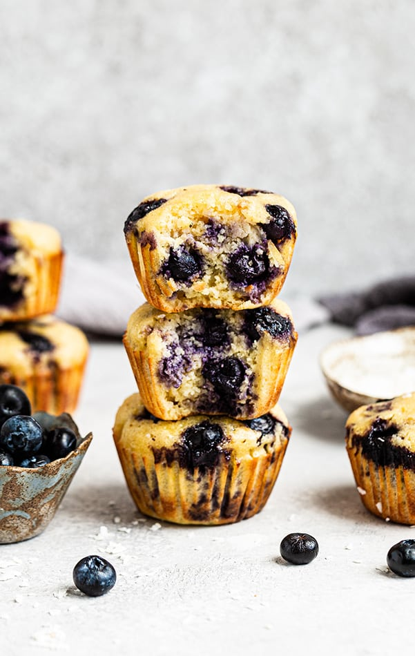 A stack of Lemon Blueberry Muffins with a bite out of a couple