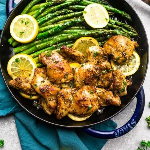 Instant Pot Lemon Butter Chicken on a cast iron skiilet with asparagus and lemon slices