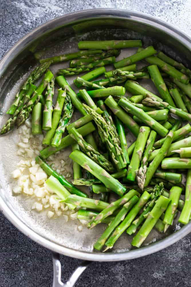 stalks of fresh asparagus sauteeing in a skillet with shallots