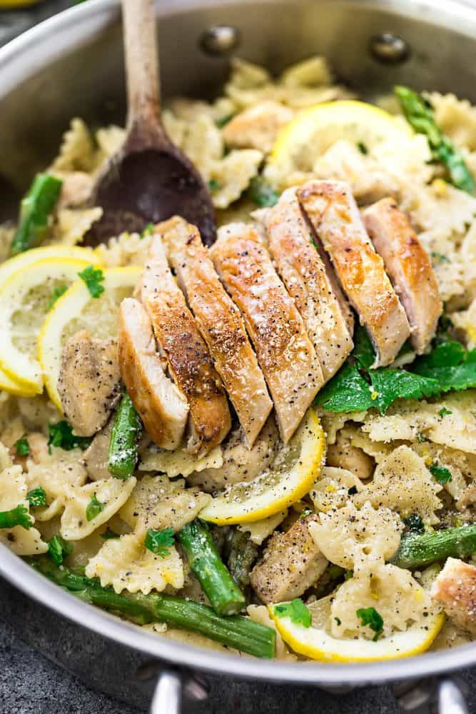 sliced lemon chicken breast sitting on top of a skillet with bow tie pasta, fresh asparagus and lemon.