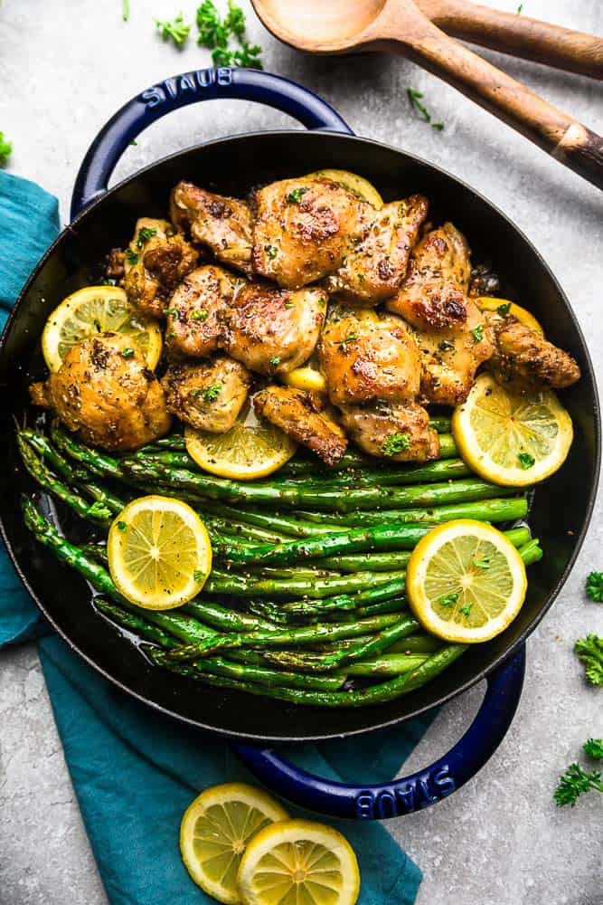 Lemon Garlic Chicken with asparagus and lemon slices in a skillet