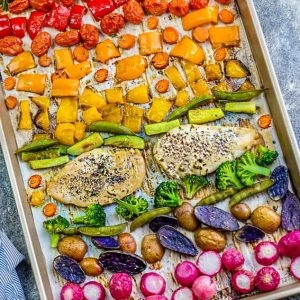 Two Lemon Herb chicken breasts with a rainbow of vegetables on a sheet pan