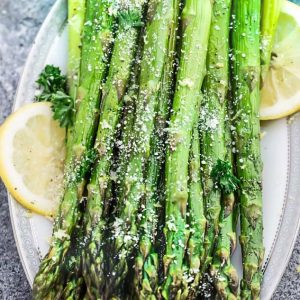 Top view of air fryer roasted asparagus on a white plate with lemon