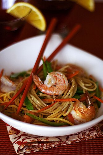 Chinese Noodles with vegetables and shrimp in a bowl with chopsticks