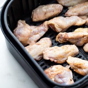 Raw chicken wings in an air fryer basket
