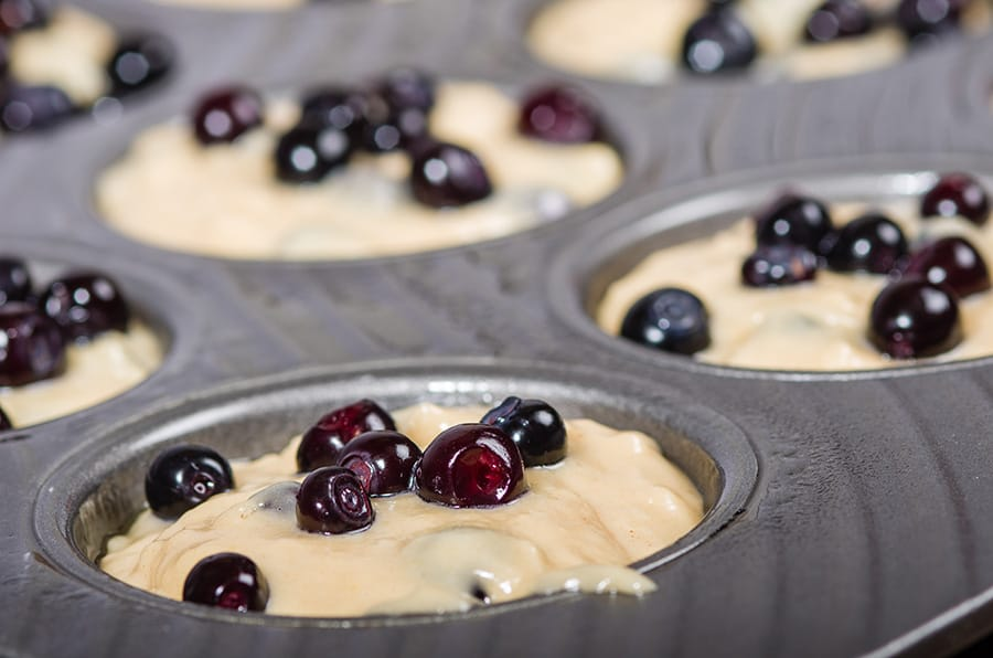 Metal muffin pan with batter and berries