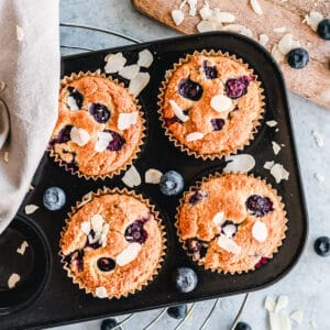 Top view of a muffin tin with four Keto Blueberry Muffins