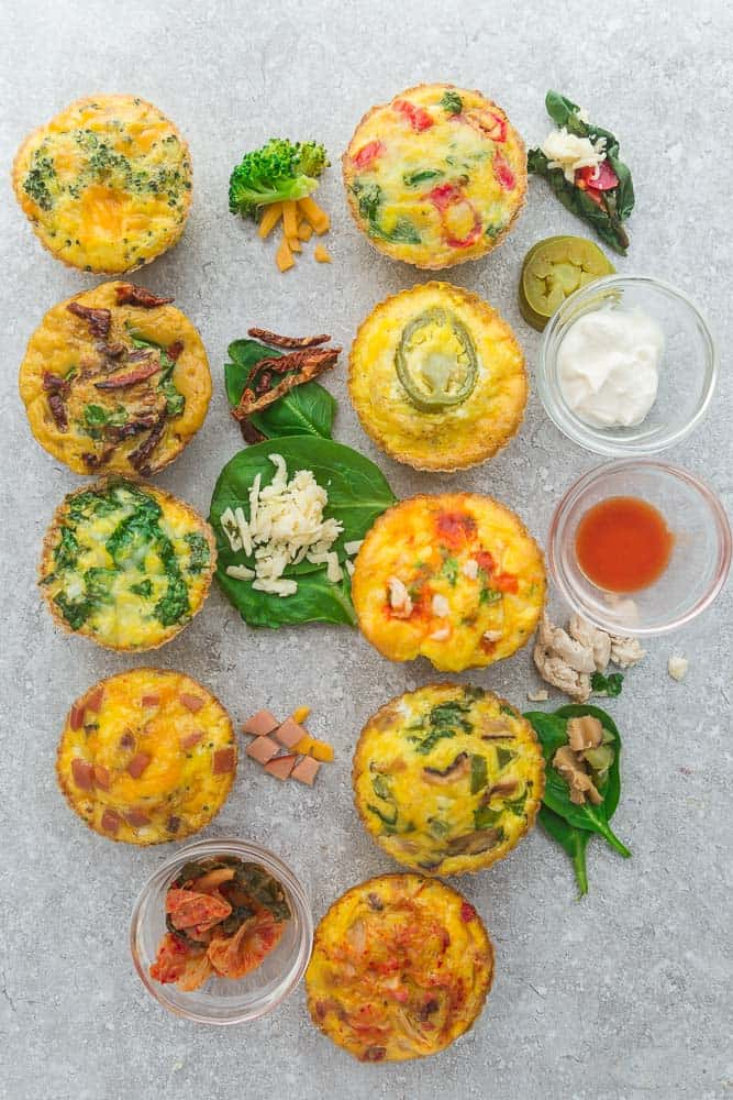 Nine Breakfast Egg Muffin Cups on a Granite Countertop with Various Dips and Ingredients in Small Cups