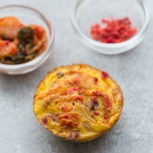 A Kimchi Egg Muffin Cup Sitting on a Gray Surface with Two Small Dishes Next to it