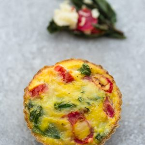 A Tomato, Parmesan and Spinach Breakfast Muffin on a Counter with Fresh Basil and Tomato