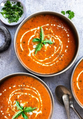 Top view of three bowls of creamy tomato soup on a grey background