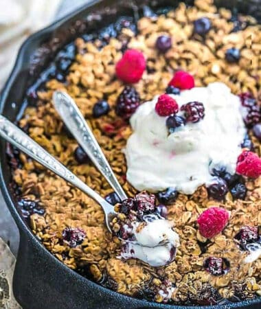Close up view of Low carb Keto Berry Crisp with blueberries, blackberries and raspberries in a cast iron skillet with two spoons and low carb ice cream
