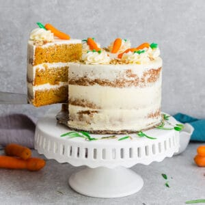 Side view of Low Carb Keto Carrot Cake on wooden cake stand with chopped pecans and carrots