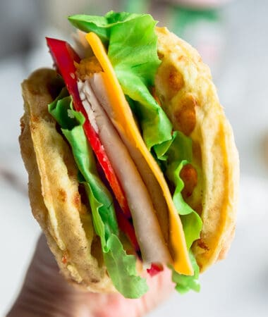 Side view of chaffle sandwich with a hand holding it up