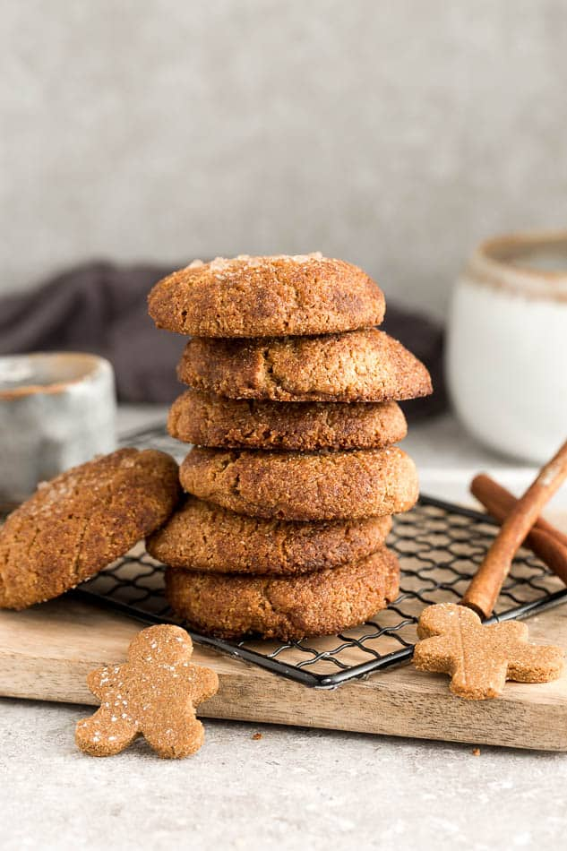 Side view of 7 stacked low carb vegan soft ginger molasses cookies on a wire rack on a grey background