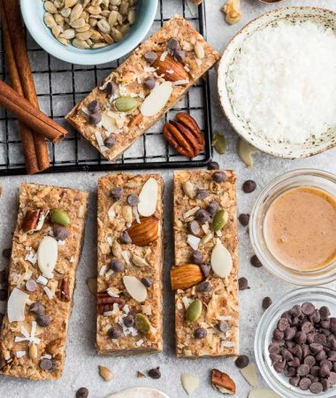 Top view of 4 keto granola bars on a grey background with ingredients