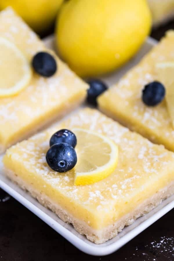 Low Carb Keto Lemon Bars on a white square plate with one blueberry